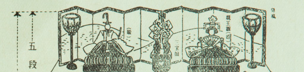Black and white illustration showing the top tier of a hinamatsuri dolls set. The Emperor on the left and Empress on the right with flowers between the couple.