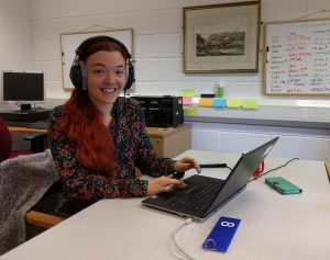 A woman smiling at the camera while wearing headphones at a computer