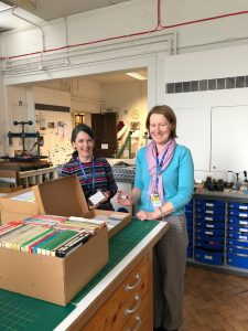 Two women stood inside Gloucestershire Archives holding tapes