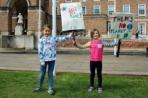 """Photograph of two children from youth strike 4 climate holding placards saying """"Save our planet""""."""