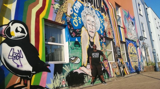 Roger Griffith MBE stood in front of a colourful graffiti'd wall in Bristol