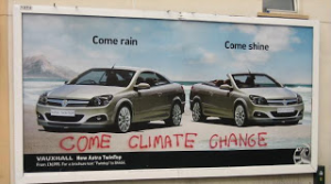 A billboard advertising a convertible car with the slogan 'Come Rain, Come Shine'. Graffiti over the top reads 'Come Climate Change'