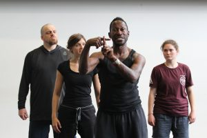 Four performers, Deaf and hearing, in rehearsal. Third performer from left looks straight ahead and is using British Sign Language; ; the other three are looking at him.