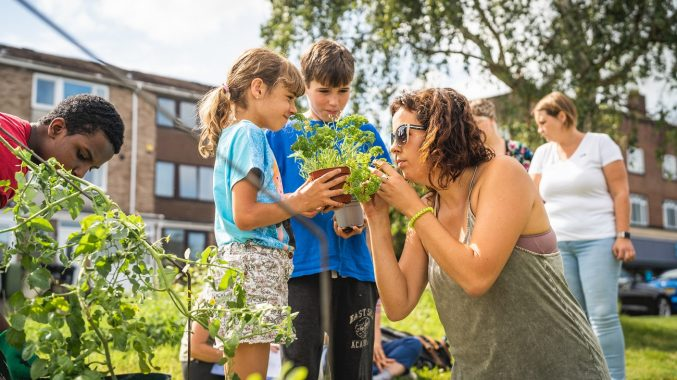 A boy and girl hold a pot of parsley for a woman to smell. An older boy to the left tends plants, and two women are talking in the background. It's a sunny day in a green space near some houses.