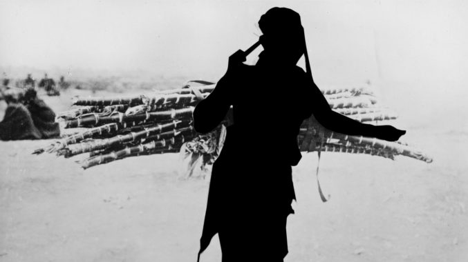A black and white photograph from the British Empire & Commonwealth Collection of a East African woman carrying cane. The woman has been obscured so only her silhouette is visible.