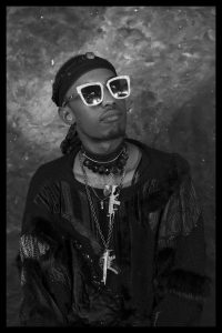 A stylish young Black man wearing sunglasses and adorned in jewellery