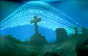 Photograph of grave stones using pinhole method. One being in the shape of a cross, the another a rectangle. It is a dark image appearing to be warped.