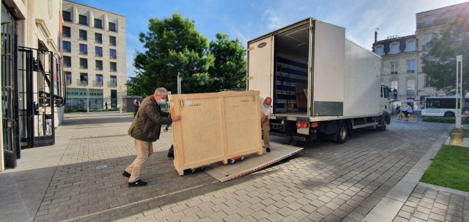 Two men unloading a painting encased in a wooden crate from a lorry in Bordeaux