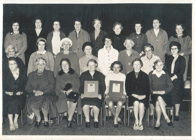 Black and white photograph of 24 women in three rows smiling at the camera.
