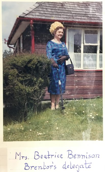 photograph of Beatrice Benneson in a blue dress, yellow hat and black gloves and handbag. She is standing in front of a house.