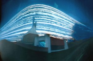 Photograph of Clifton Cathedral using pinhole method. It is a dark image with bright streaks of light, the cathedral appears to be warped towards the foreground due to this techique