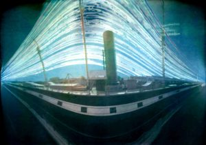 Photograph of SS Great Britain using pinhole method. It is a dark image with the ship appearing to be warped.