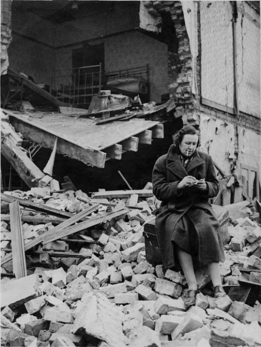A woman sits in the ruins of her bombed out house.