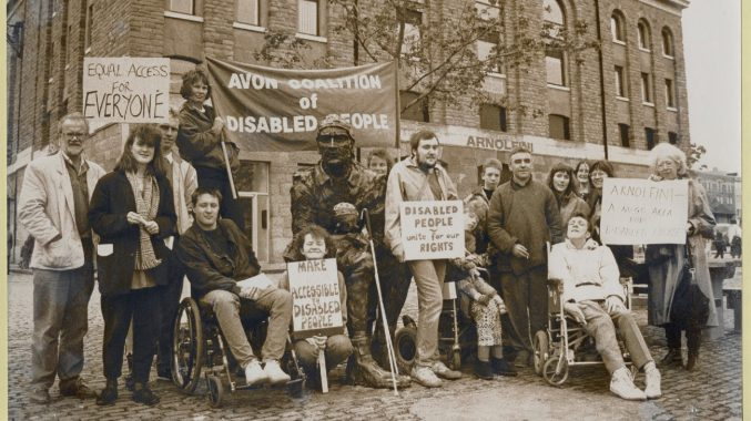 Black and white photograph of the Avon coalition of disabled people. There is a group of people with placards