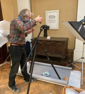 Photograph of our digitisation officer David taking a picture of a plate. The plate is on the ground and the camera is in a tripod pointing towards it. David is positioning the camera.