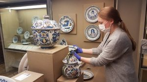 Photograph of delftware being put on display by a women in blue rubber gloves and mask on