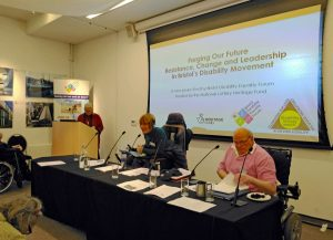 """Photograph of a meeting / seminar with two people sitting at a table facing the room looking at notes. Next to them is a man on a podium. Behind them is projector screen with """"Forging Our Future Resistance, Change and Leadership in Bristol's Disability Movement"""""""
