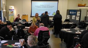 """Photograph of what looks like a seminar or meeting. There are people around several tables and a screen with a slide that says """"Forging our future: Resistance, Change and Leadership in Bristol's Disability Movement"""""""