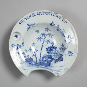 """A photograph of a plate with blue drawings of flowers and bamboo. At the top of the plate going around the the rim, are the words """"Sir your quarters up"""". There is a big piece missing out the bottom portion of the plate."""
