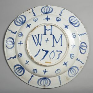 The back of a delftware plate with the initials W H M/1703