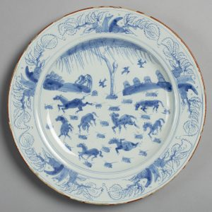 A Photograph of a plate with the blue paintings a horses in a field. There seems to be a large tree and several soaring birds.