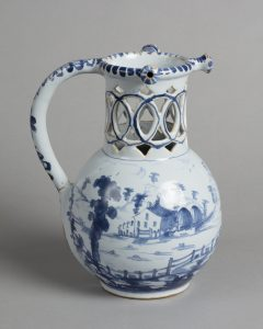 The side view of a delftware puzzle jug with a blue pattern depicting a hilly landscape with trees and a fence