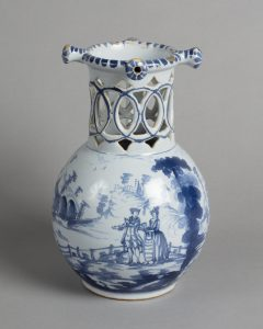 The front of a delftware puzzle jug with a blue pattern depicting a couple walking in a hilly landscape