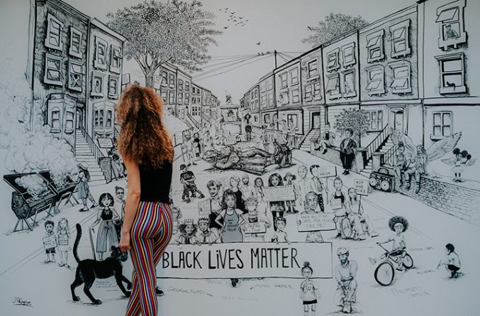 A young woman in stripy trousers and a black top drawing a large black and white mural