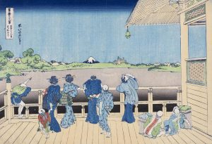 A Japanese print showing a number of people standing on a decked platform and gazing out over Mount Fuji