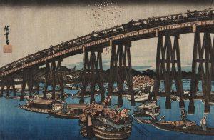 A Japanese Print of fireworks above a bridge