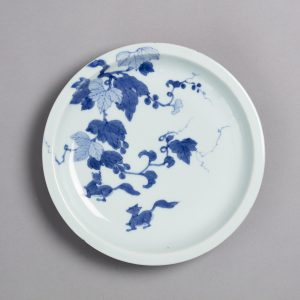 A white dish with a blue pattern of grapevines and squirrels