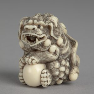 A tiny netsuke (intricate Japanese carving) of a A tiny netsuke (intricate Japanese carving) of a shishi lion clutching a ball