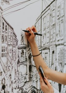 A close up of a woman's arm holding a black pen as she draws a figure on top of the Colston plinth