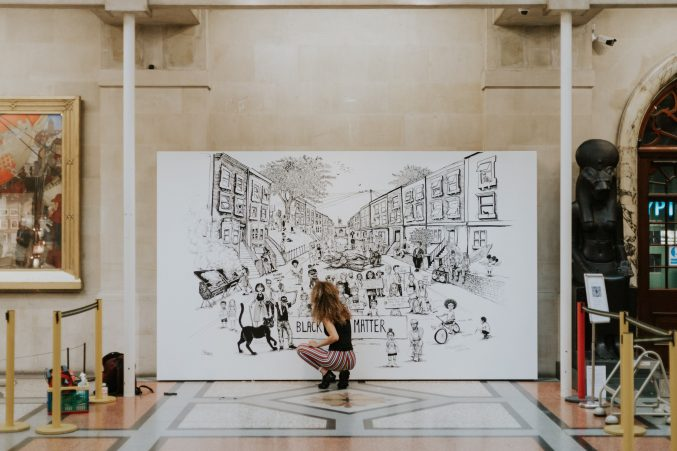 A young woman kneeling down as she works on a large black and white mural inside Bristol Museum
