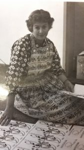 Theresa Knowles, who recorded an oral history describing her work as a teacher, musician and artist in Southern Africa. The photograph is in black and white. She is sitting on the floor with a book in the hand smiling at the camera