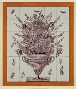 A tile depicting a vase filled with flowers with dragonflies around the outside