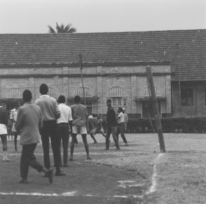 Black and white photo of people playing volleyball.