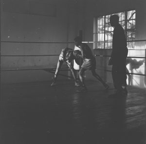 Black and white photograph by Dorothy Myers of two men in a boxing class in a Nairobi community centre. There is a man observing them.