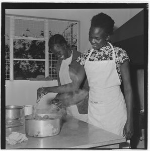 Black and white photograph by dorothy myers of two women in a kitchen with white aprons on stirring food in a pot.