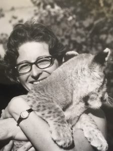 Black and white photo of Dorothy Myers holding a lion club. She is smiling at the camera